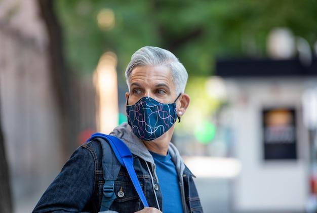 Męski turysta w masce iz plecakiem spacerując ulicą w madrycie i podziwiając widok na miasto
