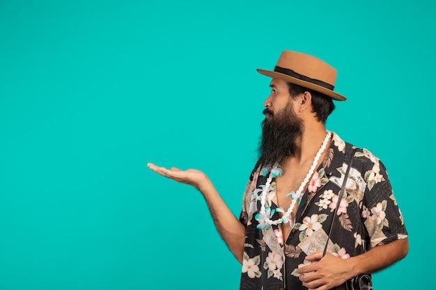 Męski turysta z długą brodą w kapeluszu i trzymający aparat na niebiesko.