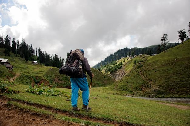 Męski turysta z plecakiem stoi blisko rzeki