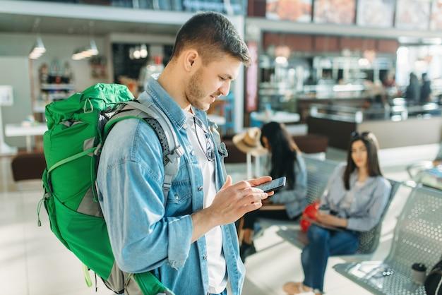 Męski turysta z plecakiem trzyma telefon komórkowy, kobiety czekają na odlot na lotnisku.