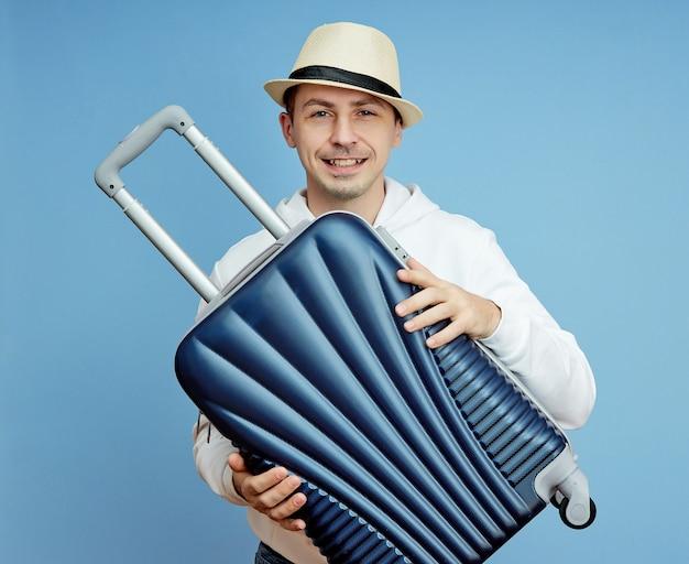 Męski turysta z walizką w ręku, bagaż podręczny turysty