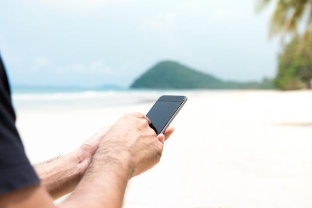 Męski turystyczny używa smartphone na wyspie przy plażą w wakacje
