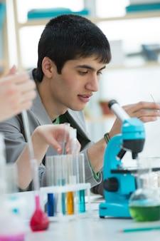 Męski uczeń pracuje z mikroskopem i różnymi cieczami w szkole, szkoła wyższa lub uniwersyteta laboratorium ,.