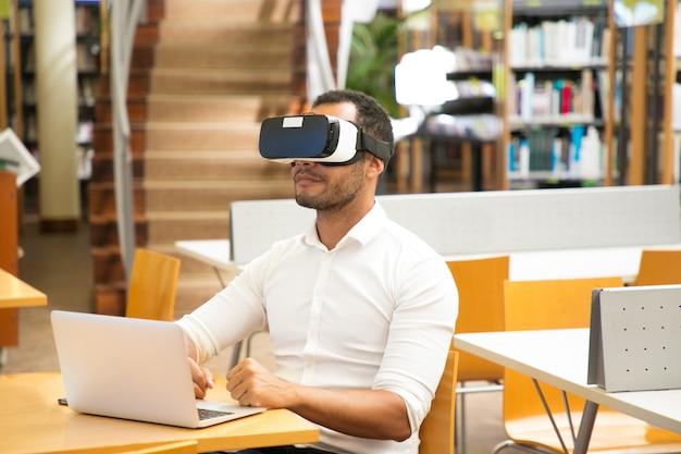 Męski uczeń używa vr słuchawki podczas pracy w bibliotece