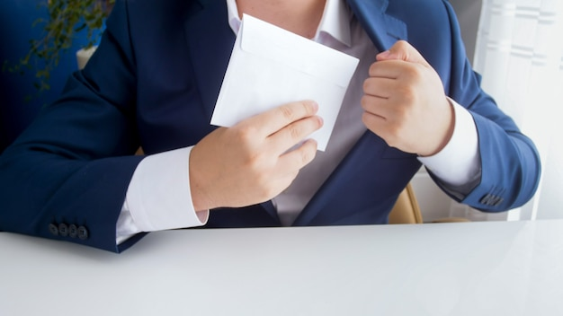 Męski urzędnik biorący łapówkę w kopercie i wkładający ją do kurtki