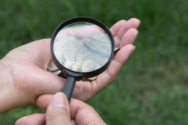 Męski używa powiększać - szkło spojrzenie przy monetami na ręce
