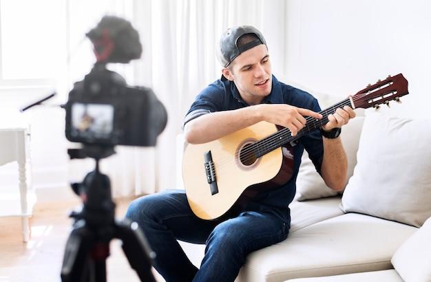 Męski vlogger nagrywa muzykę odnosić sie transmisję w domu