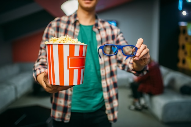 Męski widz z okularami 3d i popcornem w sali kinowej przed seansem. człowiek w kinie, rozrywkowy styl życia