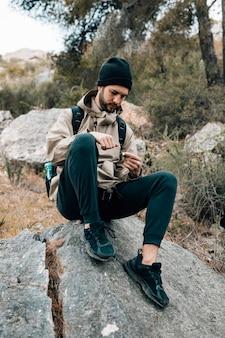 Męski wycieczkowicz siedzi na skale patrzeje nawigacja kompas