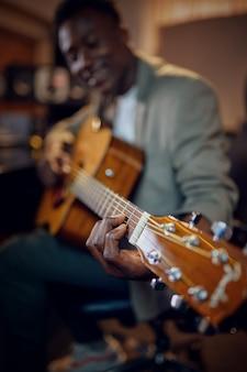 Męski wykonawca z gitarą, wnętrze studia nagrań na tle. syntezator i mikser audio, miejsce pracy muzyka