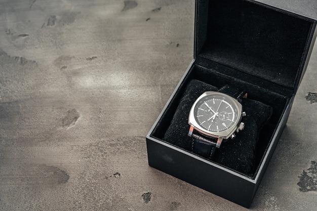 Męski zegarek mechaniczny na ciemnej powierzchni betonu z bliska