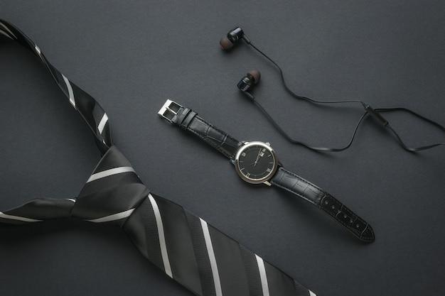 Męski zegarek ze wskazówkami, słuchawkami i krawatem na czarnym tle.
