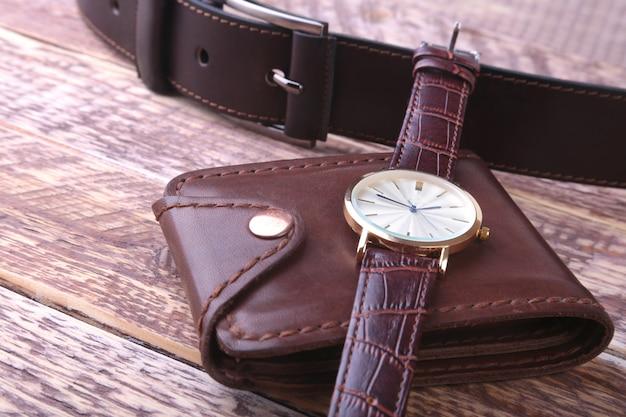 Męskie akcesoria z brązowym skórzanym portfelem, paskiem i zegarkiem.