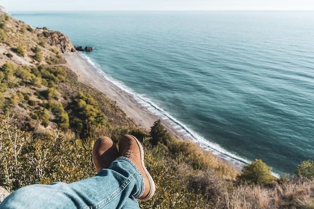 Męskie buty i nogi z wybrzeżem w tle. pojęcie eksploracji i przygód