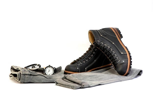 Męskie czarne buty z szarymi dżinsami i zegarkiem odizolowywającymi na białym tle.