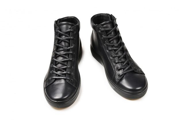 Męskie czarne skórzane buty i czarny aparat na białym na białym tle. skopiuj miejsce