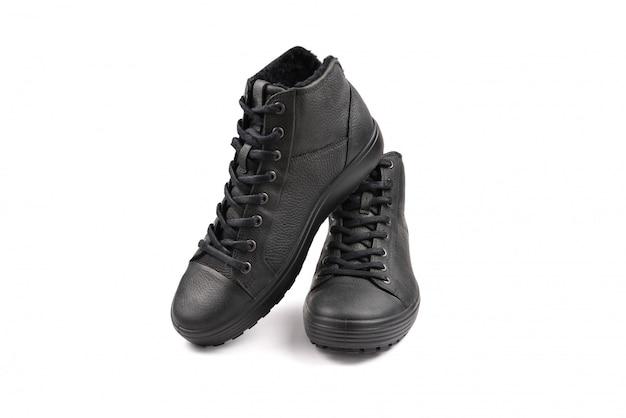 Męskie czarne skórzane buty i czarny aparat na czarnym tle. skopiuj miejsce.