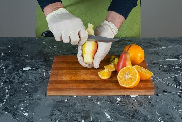 Męskie dłonie cięcia dojrzałej gruszki na marmurowym stole.
