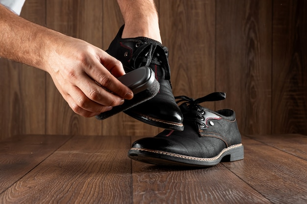 Męskie dłonie czyszczą czarne buty na drewnianej ścianie. pojęcie połysku obuwia, pielęgnacji odzieży, usług.