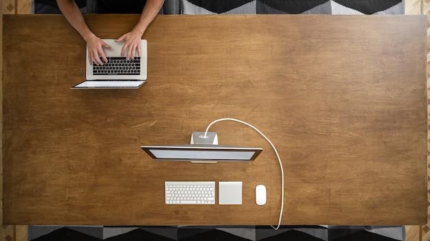 Męskie dłonie do pracy na laptopie na pustym drewnianym stole w przestrzeni coworkingowej. dwa komputery w obszarze kopiowania tabeli.