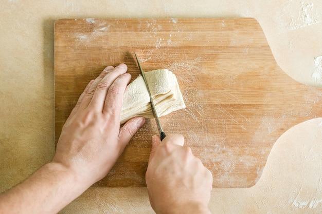 Męskie dłonie kroją surowe ciasto