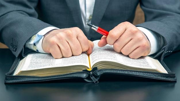 Męskie dłonie leżą na otwartej biblii z bliska. poszukiwanie boga i studiowanie książki