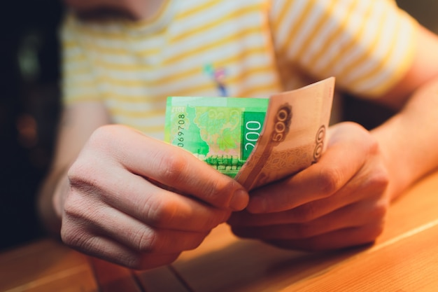 Męskie dłonie liczą rosyjskie pieniądze z bliska.