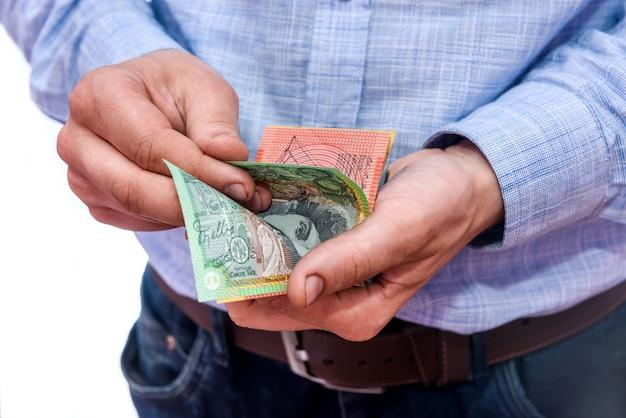 Męskie dłonie liczące banknoty dolara australijskiego z bliska