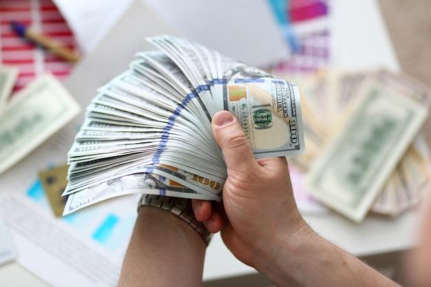 Męskie dłonie liczące pieniądze z ogromnej paczki
