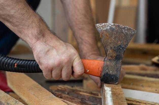 Męskie dłonie młotek gwóźdź ze starym toporem. wielofunkcyjność elementów budowlanych podczas prac budowlanych.