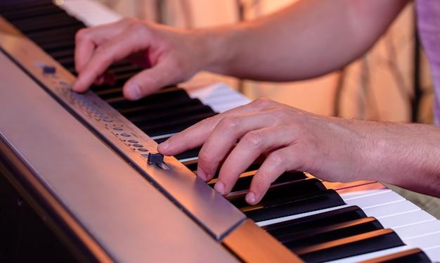 Męskie dłonie na klawiszach fortepianu na pięknej kolorowej ścianie z bliska.