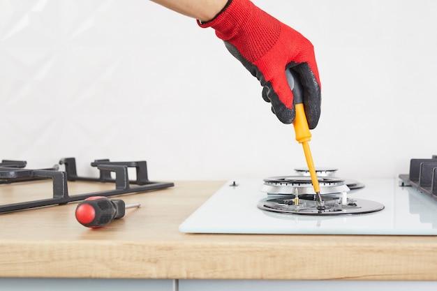 Męskie dłonie naprawiają płytę za pomocą narzędzia. technik ustawia palnik kuchenki gazowej. ścieśniać.