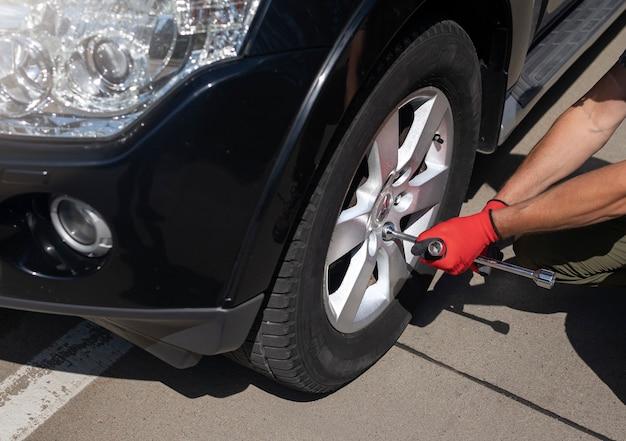 Męskie dłonie naprawiające i sprawdzające oponę koła nowoczesnego czarnego samochodu z ręcznym metalowym narzędziem z bliska
