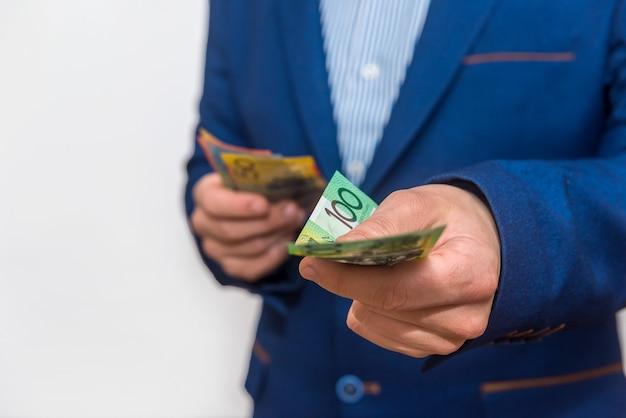 Męskie dłonie oferujące banknoty dolara australijskiego, makro