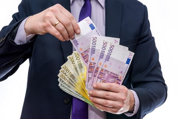 Męskie dłonie oferujące banknoty euro w wachlarzu