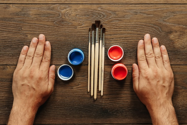 Męskie dłonie, pędzle i farba na brązowym drewnianym stole