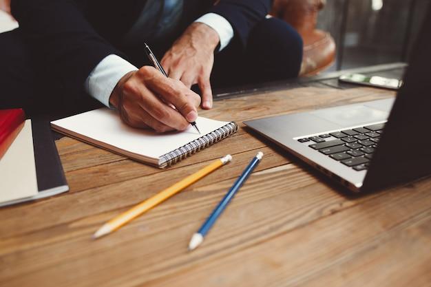 Męskie dłonie pisanie planów w notatniku.