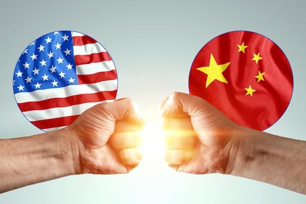 Męskie dłonie pokazują pięści na tle flag ameryki i chin.