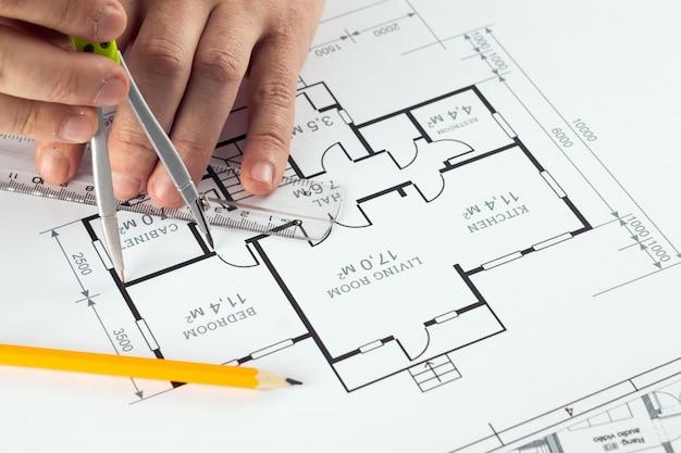 Męskie dłonie, pomarańczowy kask, ołówek, architektoniczne rysunki konstrukcyjne, taśma miernicza.
