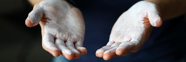 Męskie dłonie posmarowane proszkiem magnezu gotowe do treningu