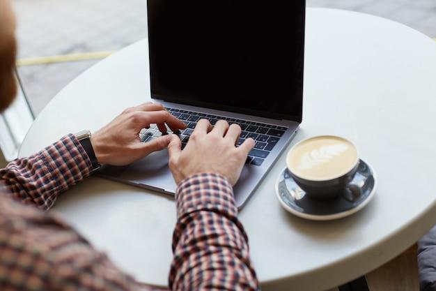 Męskie dłonie pracują na klawiaturze laptopa, prawie szara filiżanka kawy na białym stole.