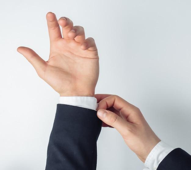 Męskie dłonie prostują koszulę na białym tle