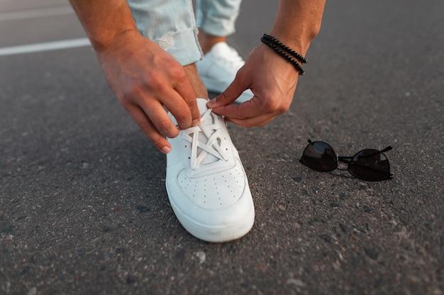 Męskie dłonie prostują sznurówki na białych modnych skórzanych trampkach. nowa kolekcja stylowych męskich butów i akcesoriów. zbliżenie.