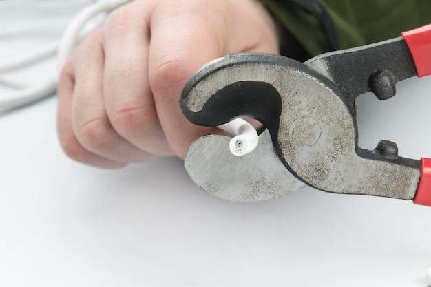 Męskie dłonie przecinają kabel specjalnym narzędziem