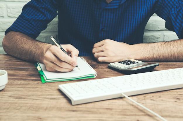 Męskie dłonie przy użyciu nowoczesnego komputera i notatnika