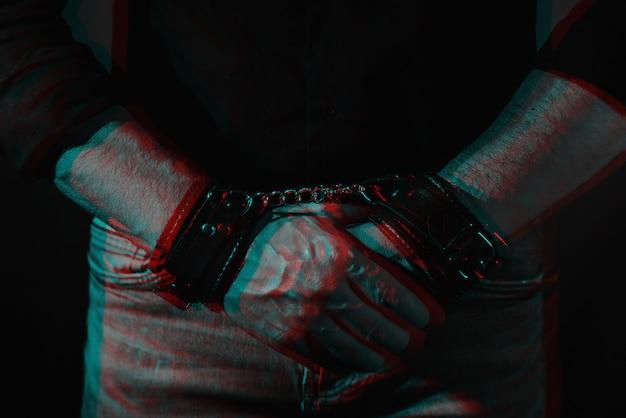 Męskie dłonie przykute skórzanymi kajdankami do bdsm