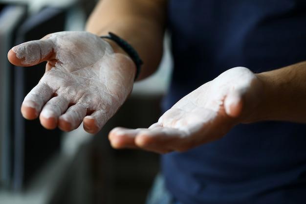 Męskie dłonie rozmazane proszkiem magnezu gotowe do treningu z bliska