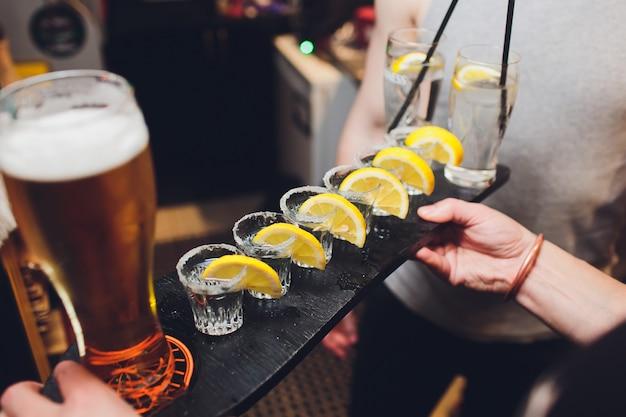 Męskie dłonie rozweselają kieliszkami kieliszka lub likieru. przyjaciele piją kieliszek lub likier i wiwatują. męskie ręki rozweselają z alkoholem na zamazanym barze przyjęcia i grzanki pojęciu.