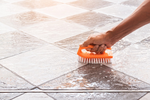 Męskie dłonie służą do przekształcania czyszczenia polerowania na podłodze z płytek.