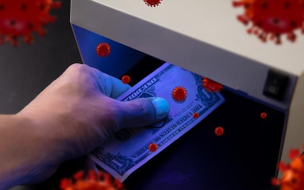 Męskie dłonie sprawdzają banknoty w detektorze modele 3d krążącego wokół koronawirusa